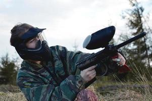 garota jogadora de paintball com uniforme de camuflagem protetora e máscara foto