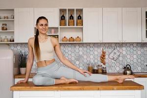 mulher atlética em roupas esportivas posando em cima da mesa foto
