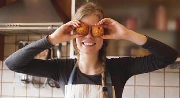 retrato de uma linda mulher de avental cobrindo os olhos com muffins foto