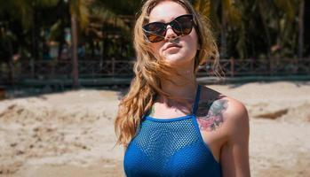linda mulher de biquíni azul em praia tropical foto