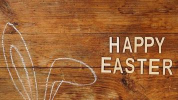 orelhas desenhadas a giz. orelhas de coelho em um fundo de madeira. Feliz Páscoa foto