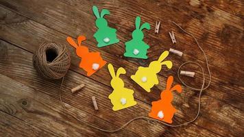 coelhinhos da Páscoa feitos de papel em um fundo de madeira foto