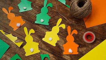 coelhinhos da Páscoa feitos de papel em um fundo de madeira. crie uma decoração foto