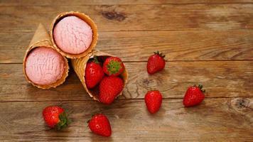 sorvete de morango em uma casquinha de waffle. frutas vermelhas e bolas de sorvete foto