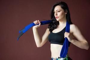 linda mulher atlética com faixa azul no fundo da parede foto