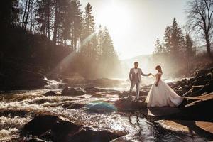 casal de noivos de mãos dadas no fundo do rio no pôr do sol foto