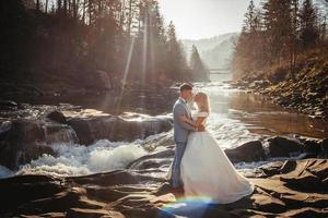 casal de noivos em um fundo de montanhas e rios no pôr do sol foto