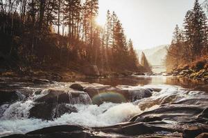 rio no fundo do cânion tendo como pano de fundo o pôr do sol foto