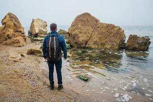 homem viajante com uma mochila em uma rocha contra um lindo mar foto