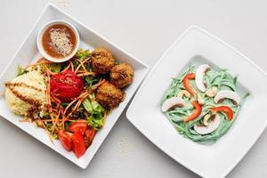 pratos brancos com pasta de legumes e falafels em um fundo branco foto