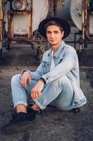 homem com chapéu sentado no skate no fundo de um prédio abandonado foto