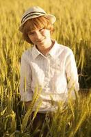 retrato de um menino entre as espigas de trigo foto