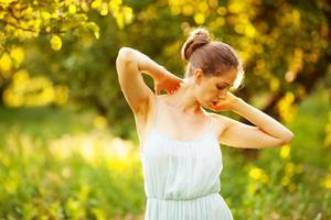 jovem mulher em um vestido sob os raios do sol da tarde foto