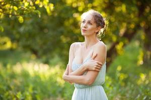 Mulher bonita com vestido azul no jardim de verão foto