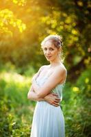 jovem com um vestido azul em um jardim de verão foto