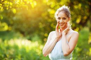 jovem alegre em um vestido sob os raios do sol da tarde foto
