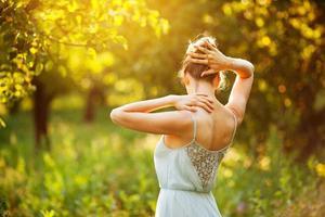 jovem de vestido azul aproveitando o sol foto