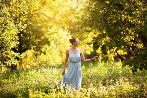 jovem de vestido azul caminhando no jardim foto