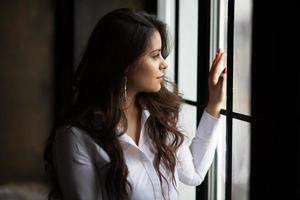 bela jovem de cabelos escuros olhando pela janela foto