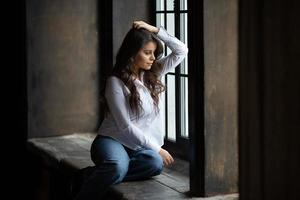 mulher de jeans senta e olha pela janela foto