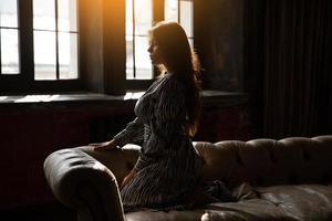 menina sentada no sofá ao sol foto