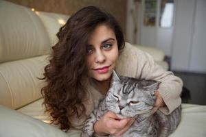 jovem acariciando um gato cinza foto