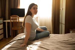 jovem senta na cama foto