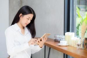 jovem mulher asiática usando computador tablet no café. foto
