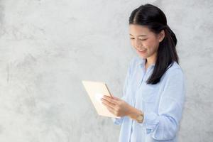 jovem mulher asiática tocar computador tablet e sorrindo. foto