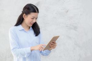jovem mulher asiática tocar computador tablet. foto
