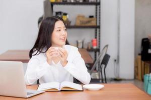 jovem mulher asiática trabalhando online no laptop e bebe café. foto
