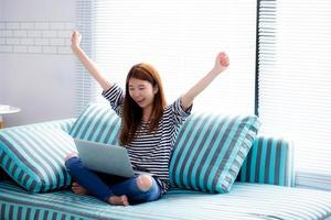 jovem mulher asiática usando laptop para lazer no sofá da sala. foto