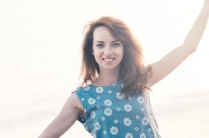 fechar o retrato de uma jovem mulher bonita com cabelo ruivo, dançando, olhos azuis e roupas, luz do sol, verão, ao ar livre, borrão de movimento, cabelo bagunçado pelo vento. Moda de rua. conceito de liberdade foto