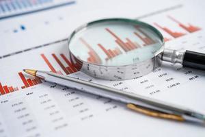 lupa em papel de gráficos de tabelas. desenvolvimento financeiro foto
