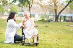 médico, ajuda e atendimento, paciente asiática idosa em cadeira de rodas no parque foto