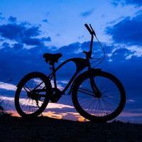 silhueta de bicicleta no lindo pôr do sol foto