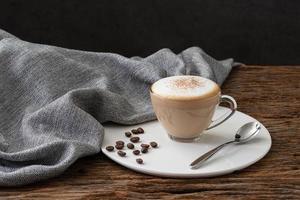copo de cappuccino café transparente com fundo de madeira foto