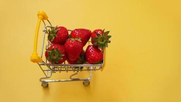 morangos frescos em um carrinho de compras em um fundo amarelo brilhante foto