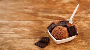 sorvete caseiro de chocolate com pedaços de chocolate em uma tigela branca foto