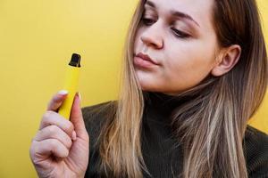 uma jovem fuma cigarro eletronico descartável foto