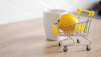 limão em um pequeno carrinho de compras na mesa da cozinha foto
