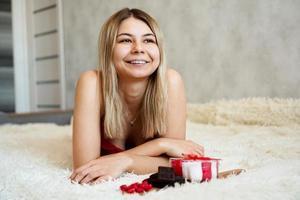 romance, conceito de presentes de dia dos namorados. linda mulher loira no sofá. foto
