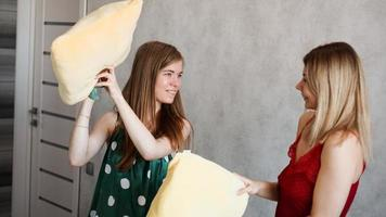 duas amigas briga de travesseiro no quarto foto