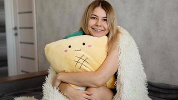 loira feliz pela manhã abraça um travesseiro amarelo. conceito matinal foto