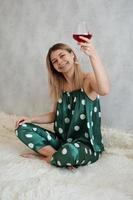 garota de pijama verde na cama com uma taça de vinho tinto foto