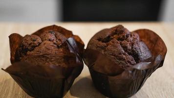dois muffins de chocolate em uma mesa de madeira contra a cozinha moderna foto