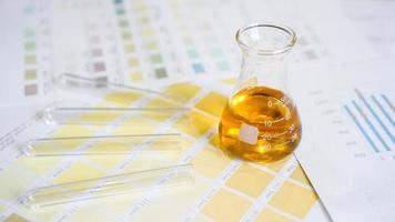 frasco e tubos de ensaio com urina em esquemas de cores médicos. foto