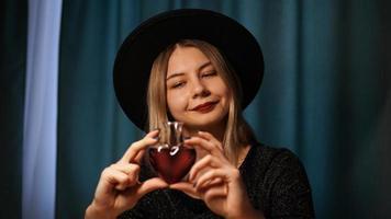 imagem recortada de mulher segurando um frasco de vidro em forma de coração com poção do amor foto