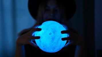 uma jovem cartomante com um chapéu está segurando uma bola mágica. foto