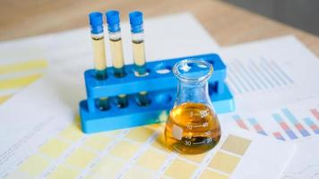 frasco e tubos de ensaio com urina em esquemas de cores médicos foto